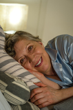 Retired smiling woman lying in bed