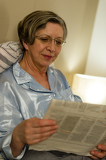 Relaxed smiling mature woman reading newspaper