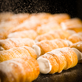 Powder sugar falling on to cream horns