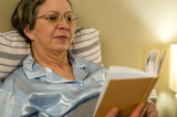 Aged woman reading book in residential home