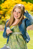 Perky female teenager texting in the park