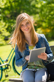Teenage girl holding digital tablet in park