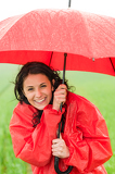 Wet young girl enjoying rainfall with umbrella