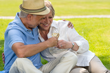 Fényképek Senior couple clinking glasses on picnic