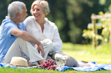 Fotografie Senior couple picnicking outdoors smiling