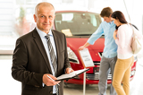 Portrait of salesman in car retail store