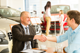 Photo Customer and car salesman shaking hands