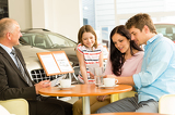 Fotografie Couple reading papers in car dealership