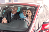 Fotografie Cheerful couple looking around in new car