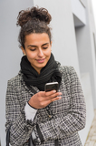 Happy woman sending text message on smartphone