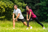 Fotografia Female and male runner stretching outdoors