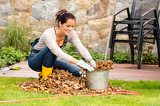Fotografie Smiling woman stuffing leaves pail autumn gardening