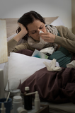 Sick woman with flu sneezing in bed