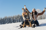 Fotografie Two girlfriends sledge downhill in wintertime