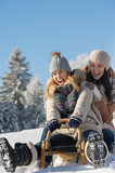 Fotografie Laughing teenagers sledge downhill in wintertime
