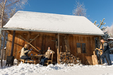 Fotografia Cozy wooden cottage winter snow people outside