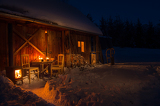 Fotografia Cozy wooden cottage in dark winter forest
