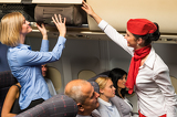 Flight attendant help passenger with luggage cabin