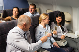 Fotografie Airplane cabin businesspeople toasting champagne