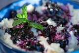Fotografie rice pudding with blueberries in the blue bowl selective focus focus on the front