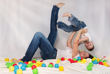 mother playing with his son among colorful balls