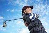 pretty young lady golfer view from below against a blue sky