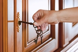 locking up or unlocking the door with a key in hand