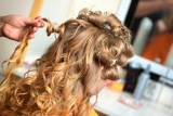 the hairdresser does a hairstyle to the bride