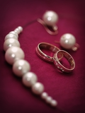 pair of wedding rings with beads on purple background