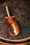 Fotografia copper spoon in coffee beans with a beautiful light