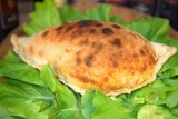 chicken calzone pizza on lettuce leaves