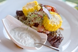 Fotografie beef steak with garlic dip sauce garnished with corn and herbs