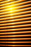 sun shining through yellow horizontal jalousie out of wood