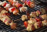 meat skewers and vegetables on the grill