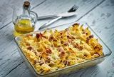Fotografia baked pasta with smoked meat drizzled with olive oil