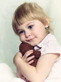the small beautiful girl embraces an amusing bear cub