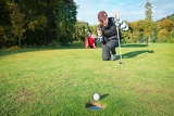 female  golf player on knees and arms raised with putter in hand in winner pose on golf green being overjoyed as golf ball drops into hole