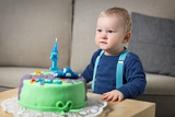 little baby celebrating its first birthday in front of him cake with candle in the form of 1