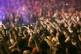 Photo crowd at a music concert audience raising hands up