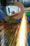 Fotografie yellow hot sparks at grinding steel material