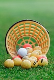 Fotografie golf balls pouring out of basket onto grass