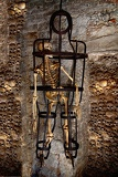 a skeleton chained in the metal cage in a cave