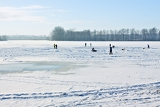iceskating on frozen lake behind sunny of the day