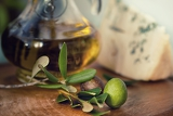 Fotografia bottle of olive oil on old wooden table and an olive branch