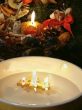 christmas still life and candles floating in plate
