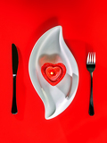 Fotografie candle shaped heart on white plate and red background