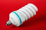 Fotografia economic light bulb standing on red background green power