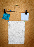 Photo paper of note with tack on cork noticeboard