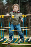 little boy climbing a rope bridge in playground