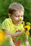 Fotografie cute 2 years old boy with dandelion outdoors at sunny summer day